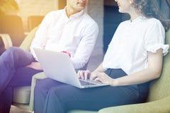 Les jeunes associés travaillent ensemble, utilisant l'ordinateur portable dans le bureau, discutant le démarrage créatif d'idée Photo libre de droits