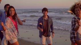 Les jeunes avec des bougies de fontaine sur la plage banque de vidéos