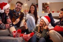 Les jeunes avec des cierges magiques appréciant en partie le jour de Noël Images libres de droits