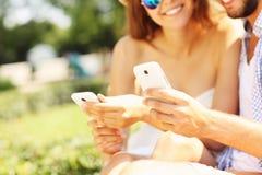 Les jeunes avec des smartphones en parc Photos libres de droits