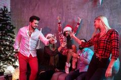 Les jeunes avec des verres de champagne à la fête de Noël Images stock