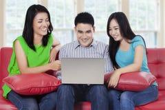 Les jeunes avec l'ordinateur portable se reposant sur le sofa Photographie stock