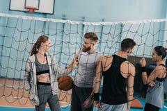 Les jeunes avec la boule tenant le filet proche dans la salle de gymnastique Photos libres de droits