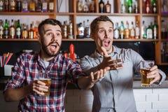 Les jeunes avec le football de observation de bière dans une barre Image stock