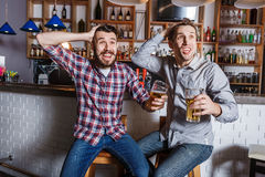 Les jeunes avec le football de observation de bière dans une barre image libre de droits