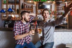 Les jeunes avec le football de observation de bière dans une barre Photo stock