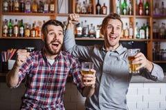 Les jeunes avec le football de observation de bière dans une barre Photos libres de droits