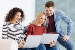 Les jeunes avec plaisir positifs regardant des ordinateurs Image stock