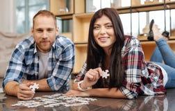 Les jeunes avec plaisir tenant des morceaux de puzzle denteux Photos libres de droits