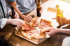 Les jeunes ayant l'amusement avec de la bière et la pizza Image stock