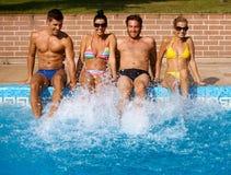 Les jeunes ayant l'amusement d'été par la piscine Image stock