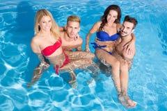 Les jeunes ayant l'amusement dans la piscine Photographie stock
