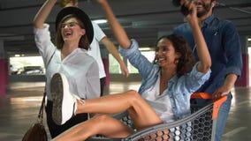 Les jeunes ayant l'amusement, emballant sur le chariot de achat au stationnement clips vidéos