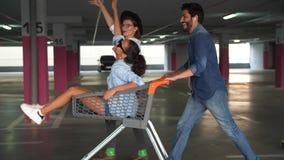 Les jeunes ayant l'amusement, emballant sur le chariot de achat au stationnement banque de vidéos