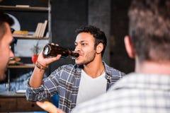 Les jeunes ayant l'amusement et buvant de la bière à la maison Photographie stock libre de droits