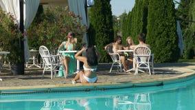 Les jeunes ayant l'amusement et détendant par la piscine banque de vidéos