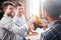 Les jeunes ayant l'amusement et faisant tinter des bouteilles à bière à la maison Photos stock