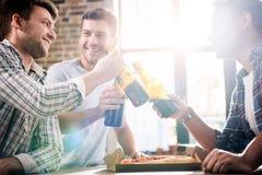 Les jeunes ayant l'amusement et faisant tinter des bouteilles à bière à la maison Photo libre de droits