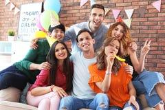 Les jeunes ayant la fête d'anniversaire dans la chambre décorée Photographie stock libre de droits
