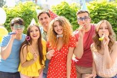 Les jeunes ayant la fête d'anniversaire dehors le jour ensoleillé Photographie stock libre de droits