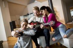 Les jeunes ayant la partie avec la guitare Photos stock