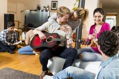 Les jeunes ayant la partie avec la guitare Image stock