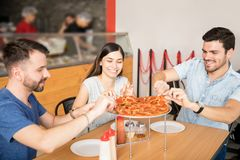 Les jeunes ayant la partie d'amusement avec la pizza délicieuse à l'intérieur Photo stock