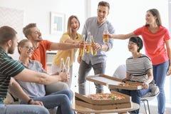 Les jeunes ayant la partie d'amusement avec la pizza délicieuse Photos libres de droits