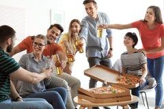 Les jeunes ayant la partie d'amusement avec la pizza délicieuse Photo stock