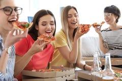 Les jeunes ayant la partie d'amusement avec la pizza délicieuse Photographie stock libre de droits