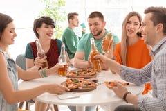 Les jeunes ayant la partie d'amusement avec la pizza délicieuse Photo libre de droits