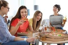 Les jeunes ayant la partie d'amusement avec la pizza délicieuse Image libre de droits