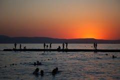 Les jeunes ayant la partie sur la plage pendant le coucher du soleil Photo stock