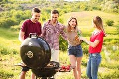Les jeunes ayant le barbecue dans la région sauvage Image libre de droits