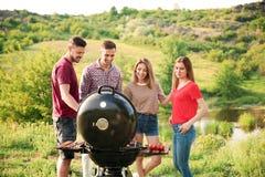 Les jeunes ayant le barbecue dans la région sauvage Images stock