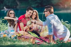 Les jeunes ayant le pique-nique près de la rivière Photo stock