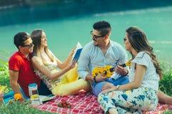 Les jeunes ayant le pique-nique près de la rivière Photo libre de droits