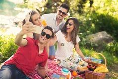 Les jeunes ayant le pique-nique près de la rivière Photographie stock