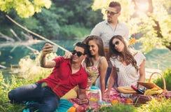 Les jeunes ayant le pique-nique près de la rivière Photos libres de droits