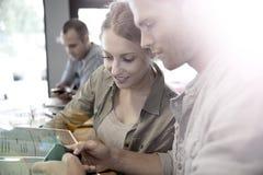 Les jeunes ayant une coupure dans un snack-bar partageant l'information sur un smartphone Image libre de droits