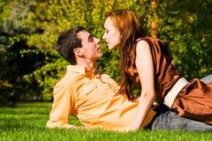 Les jeunes baisers heureux de couples sur l'herbe photos stock