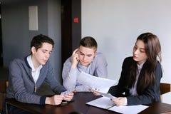 Les jeunes banquiers réussis deux types et fille vérifient et conviennent le document Image stock