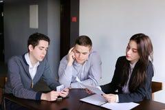 Les jeunes banquiers réussis deux types et fille vérifient et conviennent le document Images stock