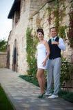 Les jeunes beaux couples élégants heureux sur le fond verdissent l'orphie Photographie stock libre de droits