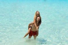 Les jeunes beaux couples ayant l'amusement voyageant ensemble en mer bleue, appréciant des vacances et voyageant, fille s'asseyan Photo stock