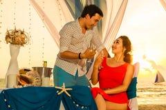 Les jeunes beaux couples dînent romantique au coucher du soleil sur un tro images stock