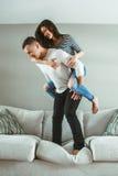 Les jeunes beaux couples drôles équipent la femme dans l'amour ayant l'amusement sautant du lit à l'intérieur à la maison Photographie stock libre de droits