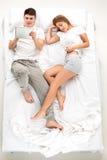 Les jeunes beaux couples se situant dans un lit avec l'ordinateur portable Image stock