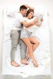 Les jeunes beaux couples se situant dans un lit avec l'ordinateur portable Photo libre de droits