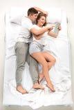 Les jeunes beaux couples se situant dans un lit avec l'ordinateur portable Images stock